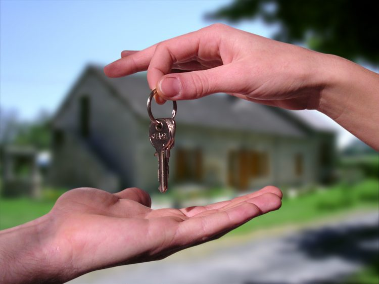 mano dà chiave ad altra mano con casa sullo sfondo