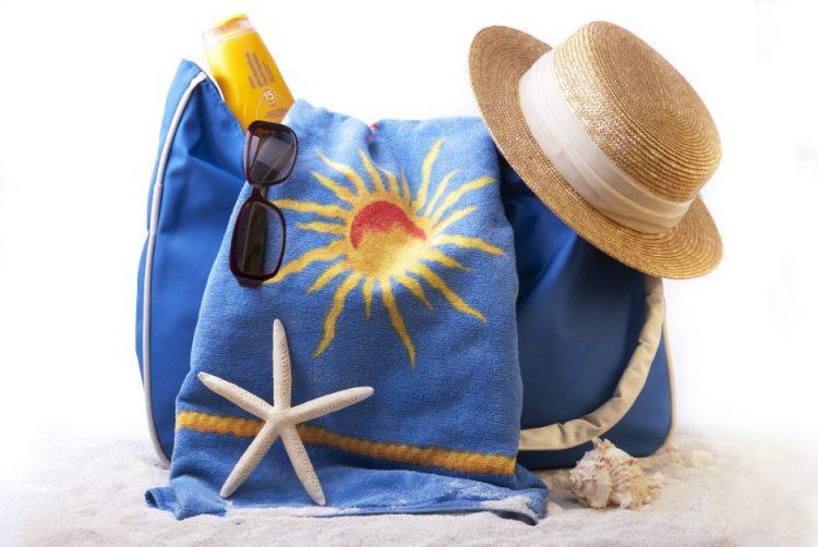 borsa da spiaggia blu con cappello di paglia e occhiali da sole